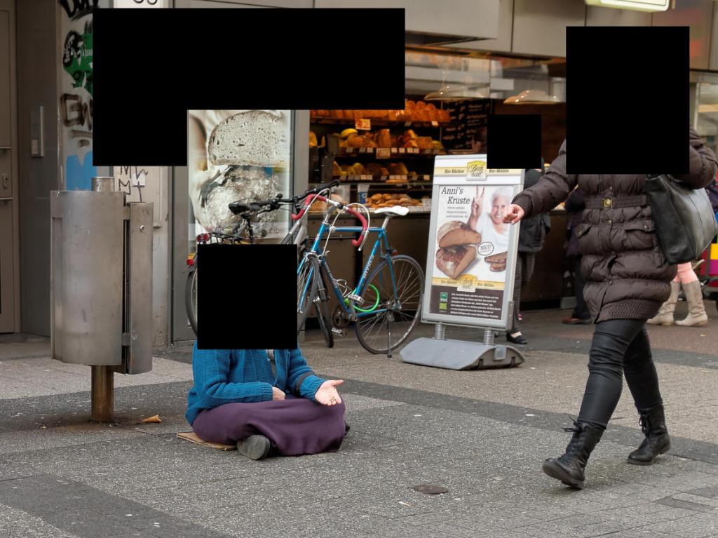 Straßenfotografie: Passantin ignoriert Bettlerin. - Afgrund der Rechtslage in Deutschland muss das Bild bis zur Unkenntlichkeit zensiert werden.